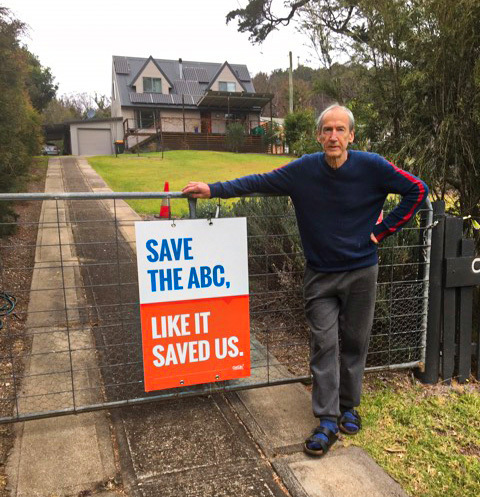 "Image of Robert, an Eden-Monaro member, standing with his ABC Yard sign that reads ""Save the ABC, like it saved us."""